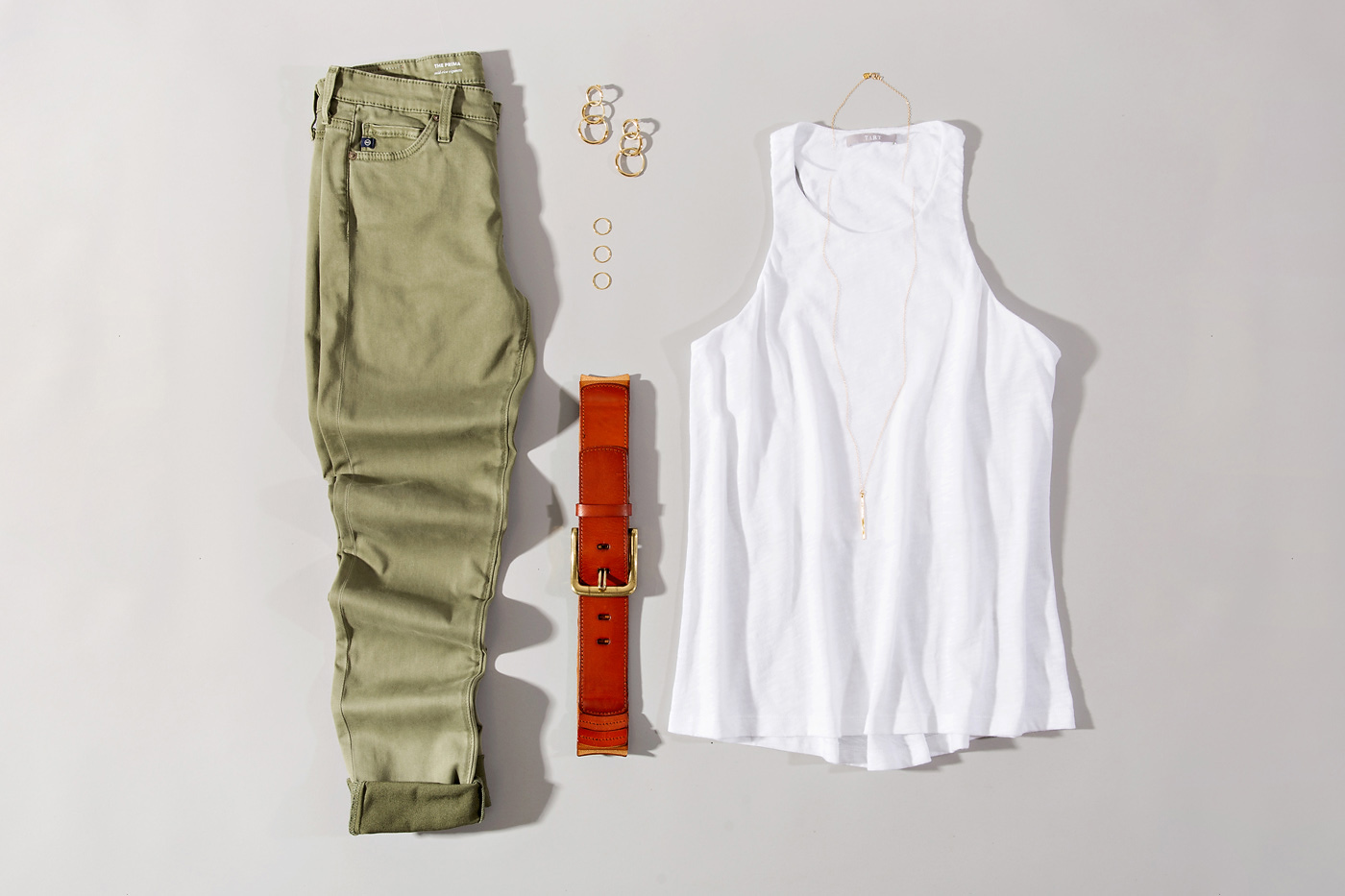 white tank styled with green skinny jeans and simple accessories